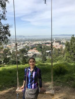 Maria poses for a photo in the hills of Berkeley with a view of the San Francisco Bay Area