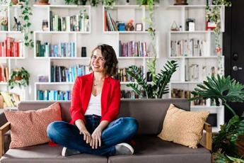 Photo of Jen Brown sitting on a couch in front of a book shelf