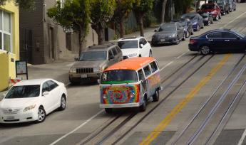 A rainbow painted van drives down a hilly San Francisco street
