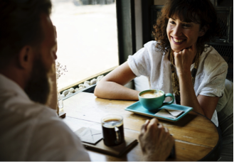Photo of two people talking while having coffee