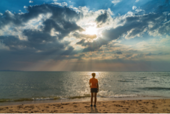 Photo of man standing on a beach looking at the sun