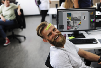 Photo of a man laughing in front of a computer
