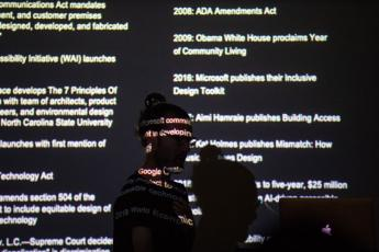 Josh walking in front of a slide which is projected on top of his face. Almost completely black, his figure is silhouetted and a timeline of significant disability design events are featured on the screen including the passage of the ADA and Microsoft's r