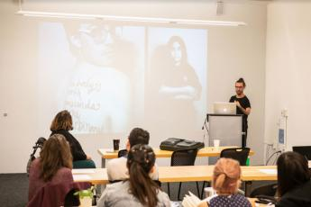 Josh giving a lecture to design students at California College of the Arts. He is joined by co-organizer, Catherine Callahan. The slide features Hannah Soyer's This Body is Worthy project—an ongoing campaign celebrating bodies that fit outside social idea