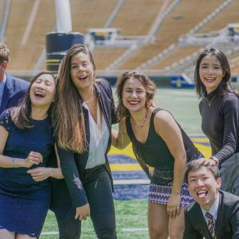 Karin and some of her friends laughing while taking a pic on the football field, in business professional attire.