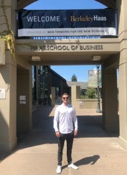 Lukas Linn stands and smiles in front of the Haas School of Business at UC Berkeley