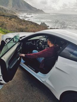 Markus sitting in the brand new 5.0 Mustang GT while looking out at the ocean