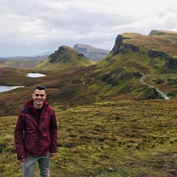 Post-Bacc Counseling graduate Michael Sanchez on a trip with valleys, winding road and mountains in the background in the Quiraing at the Isle of Skye, Scotland