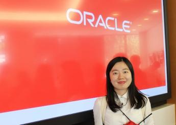 UC Berkeley Extension student in front of Oracle sign during a visit to the company.