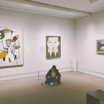 Xinyue Yang sitting on the floor of an art museum, studying. Photo.
