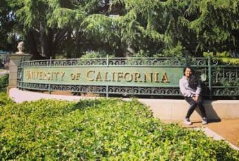 International student poses in front of UC Berkeley sign