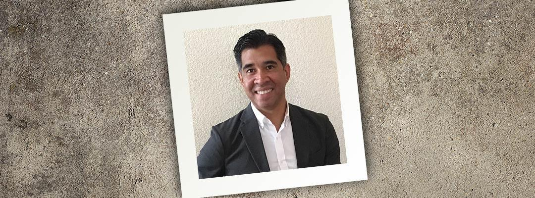 Square photograph on a granite surface at a tilt featuring College Admissions instructor Armando Diaz in an open-collar shirt and suit jacket