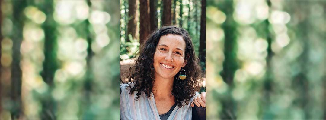 Photo of ESL Teacher Dana Neufeld in the forest wearing a rainbow shirt