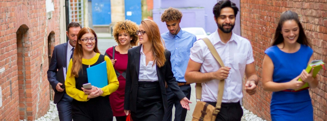A group of seven young professionals and students walks down the street