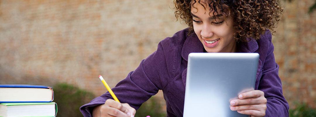 Black student learning on an tablet while taking notes on a notpad