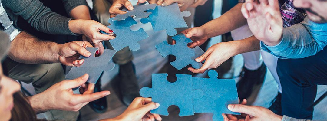 Photo of people holding jigsaw puzzle pieces