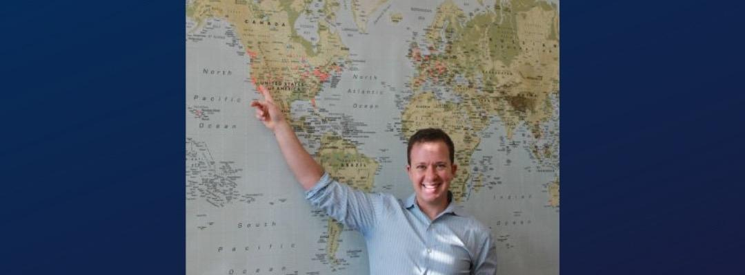 Alex Budak in front of a map of the world, pointing to Berkeley, California