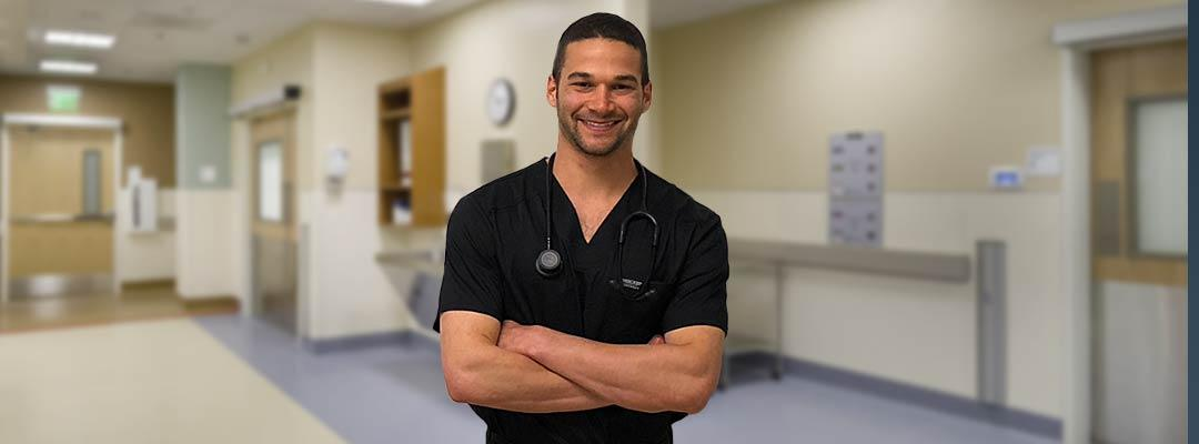 Alexander Lipson in his nursing outfit standing in front of a clinical setting