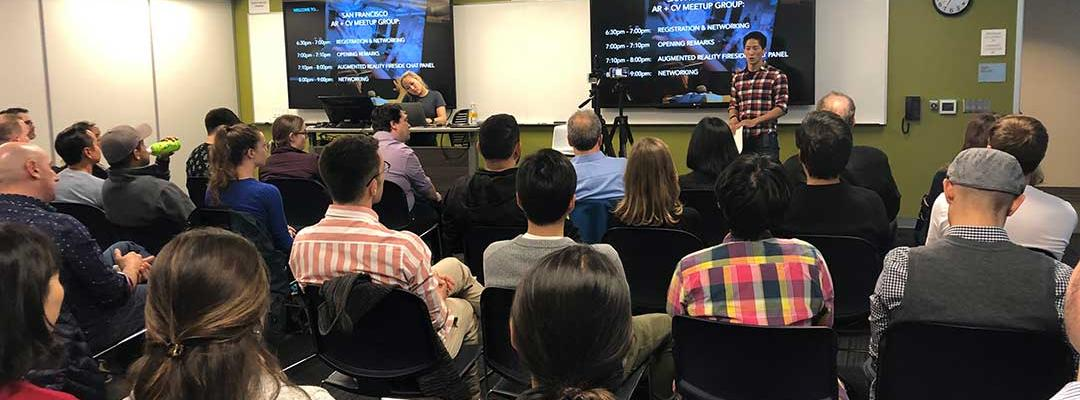 Audience seated and watching a presentation from moderator Sheng Huang in front of a plasma display