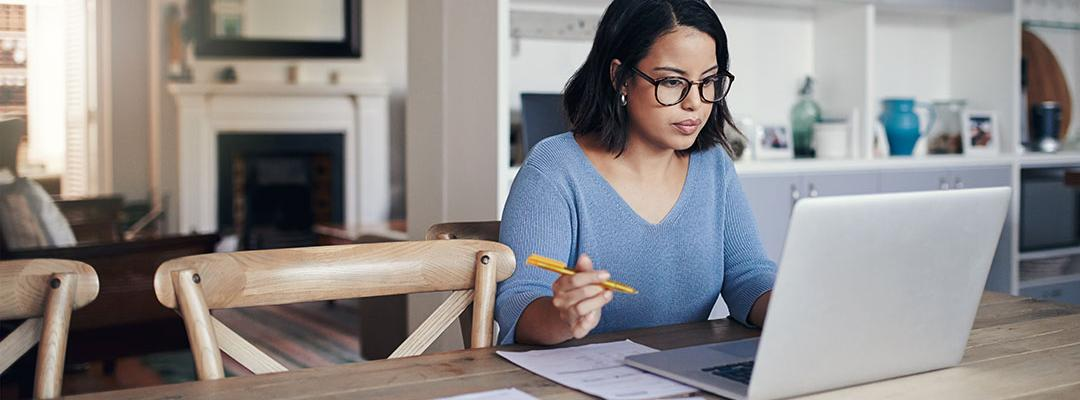 Woman sitting at kitchen table looking at laptop working on financial reports