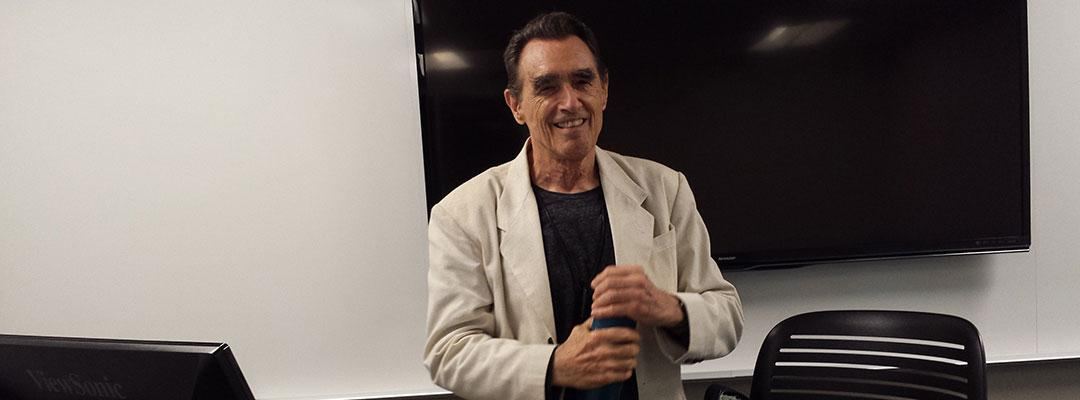 Writing instructor and poet Clive Matson standing in the front of a classroom at UC Berkeley Extension in San Francisco