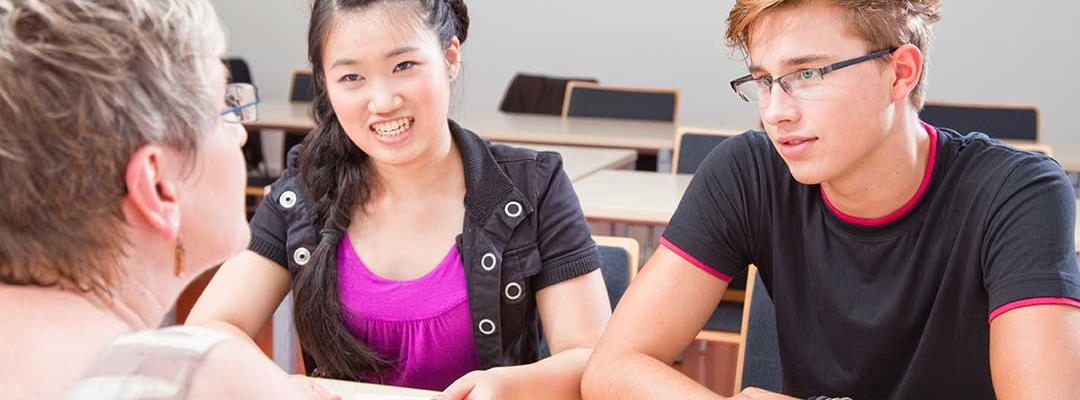 Photo of education counselor sitting at a table with a young woman and a young man