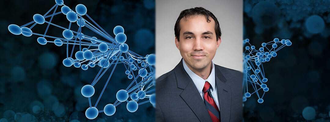 Photo of Dylan Blackburn in front of a gene illustration
