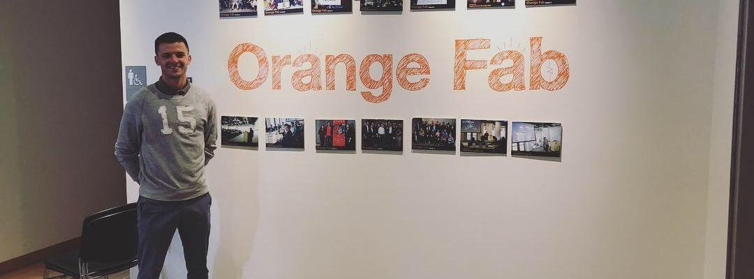 BHGAP student Marcel Marius poses in front of the Orange sign during a company site visit.