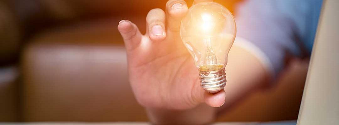 image of hand holding a lightbulb