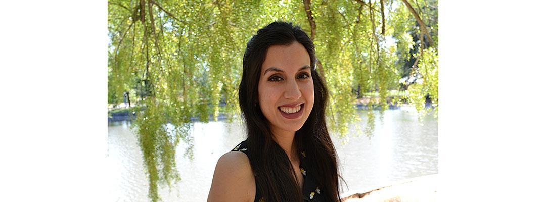 CLS Prep Program graduate Ester Fernandez standing by water, under a tree