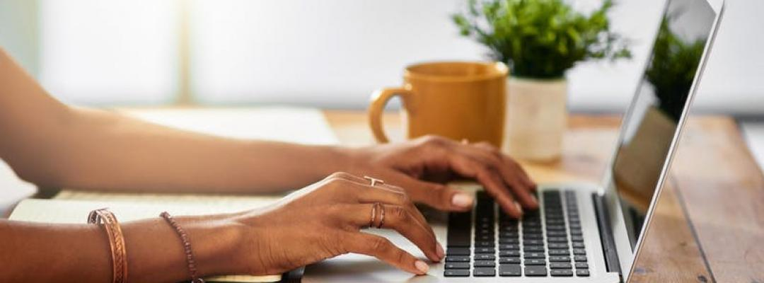 Photo of woman's hands typing on a keyboard