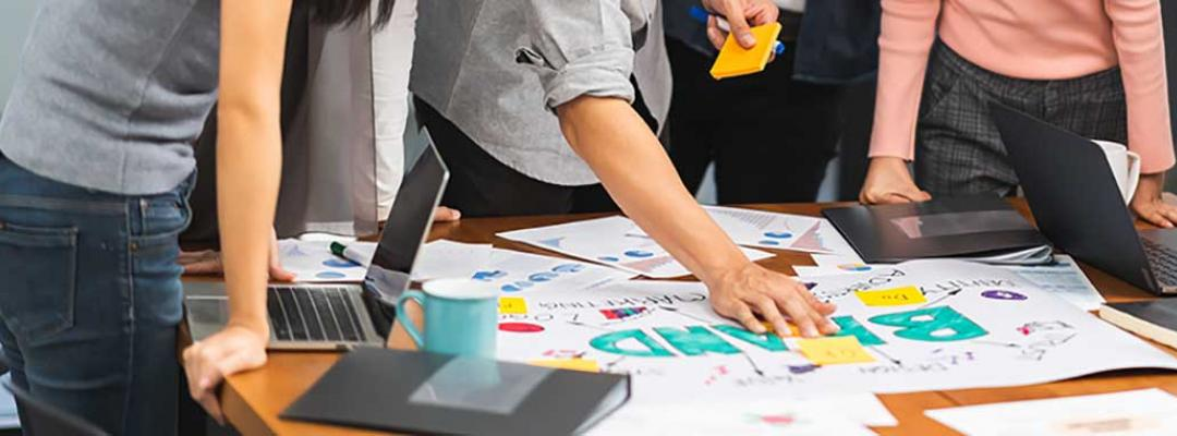 Photo of group of marketing professionals working on branding documents and sticky notes