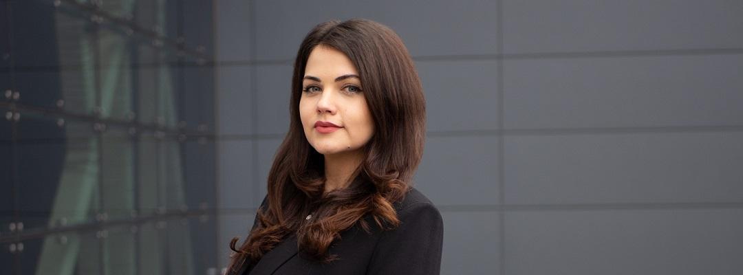 Photo of UX Design program graduate Iliyana Bozhanina in front of a dark gray building