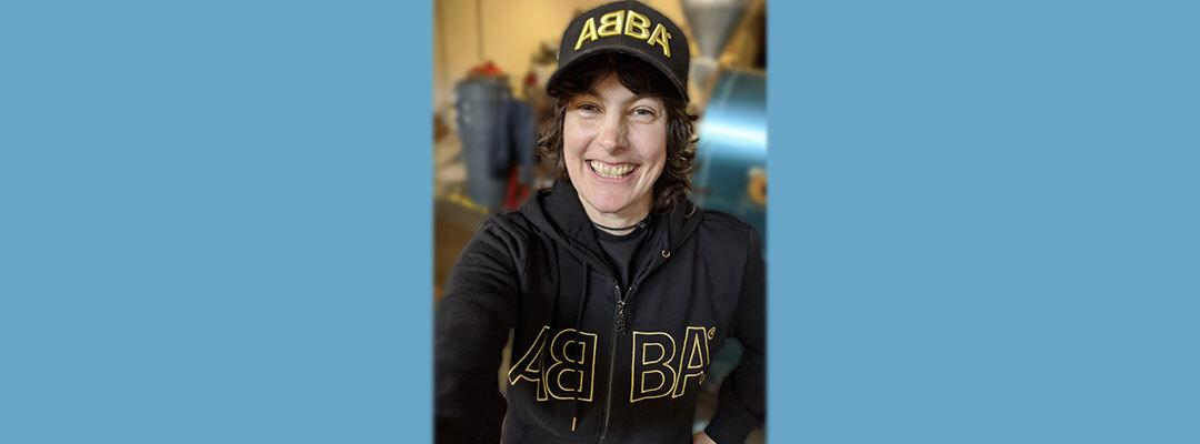 Photo of Jen St. Hilaire wearing ABBA sweatshirt and hat