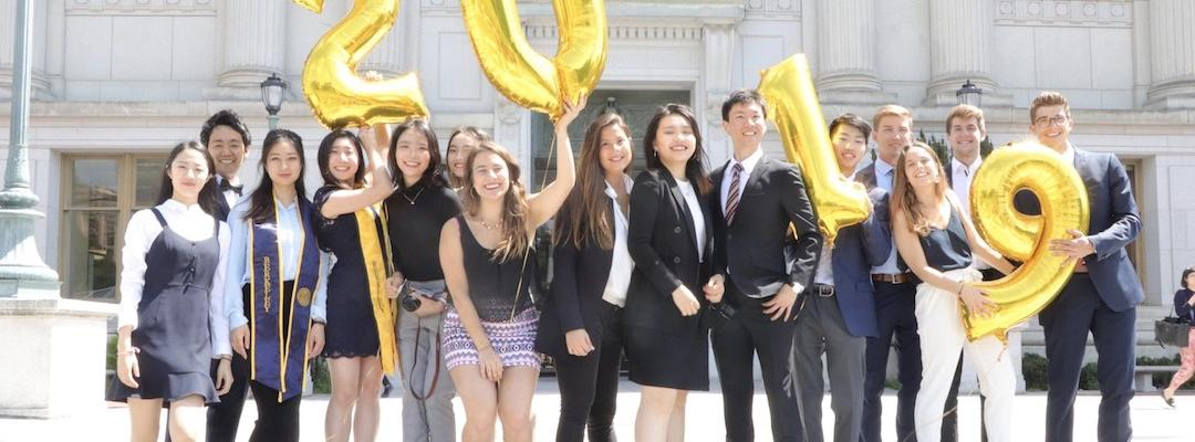 Karin and the rest of the BHGAP students smiling and posing for a picture in front of Doe Memorial Library, holding 2019 balloons in their hands.