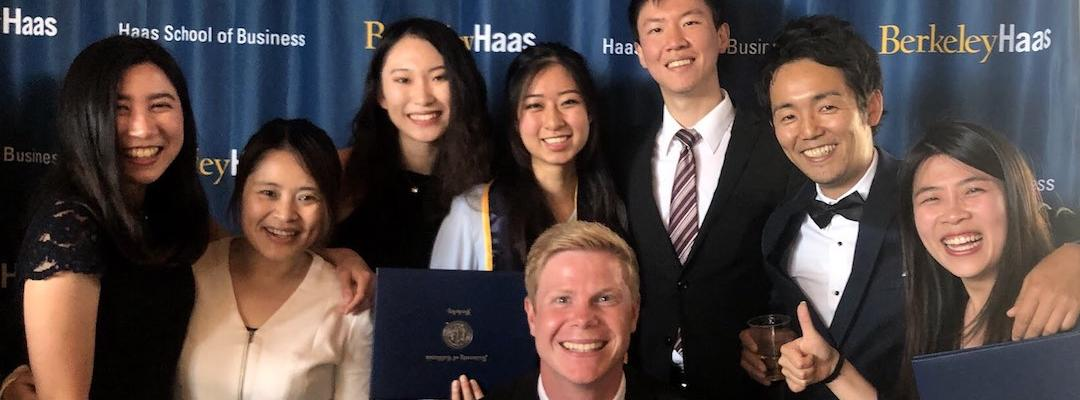 Karin and some friends posing for a picture in front of a Berkeley Haas backdrop, with some holding their diplomas from the program.