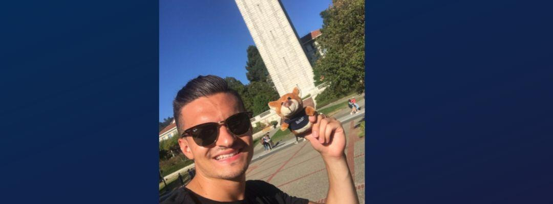 Lukas poses in front of UC Berkeley's campanille with a stuffed Oski Bear