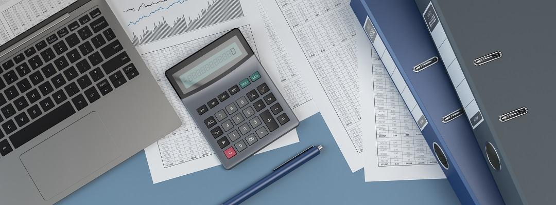 Accounting documents, calculator, laptop and binders. Stock photo.