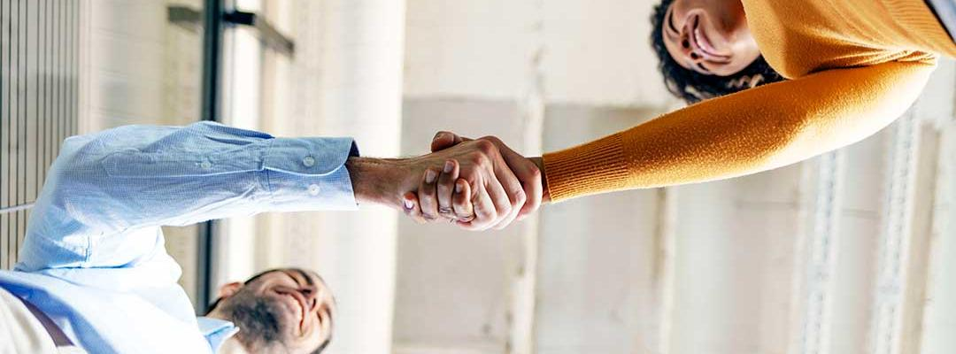 Photo looking up of two people shaking hands