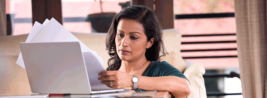photo of woman studying papers while at an open laptop
