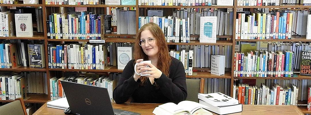 Editing student, scholarship winner Tracy Locken at a table in the library, with a laptop and books