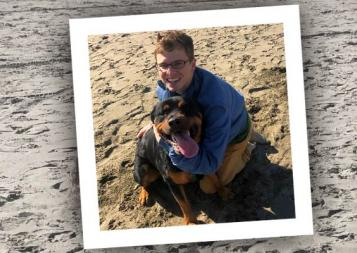 Post-Bacc Health Professions student, scholarship winner Matt Klinkel on a beach with a dog
