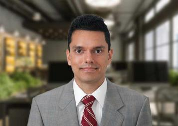Headshot of Ameer Acharya wearing a gray suit and a red tie