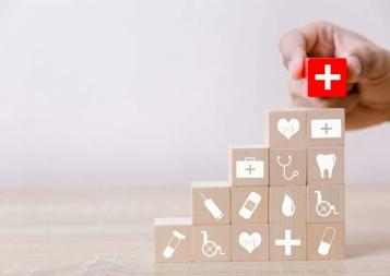 Hand stacking red block with white cross on stack of wooden blocks with medical logos