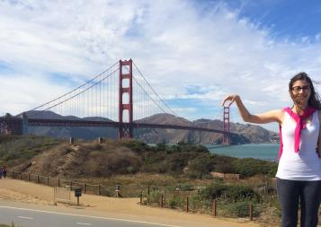 IDP graduate Maria Paula poses playfully in front of the Golden Gate bridge