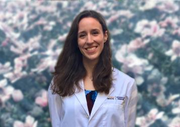 Photo of Laura Potter wearing white medical jacket in front of flower background