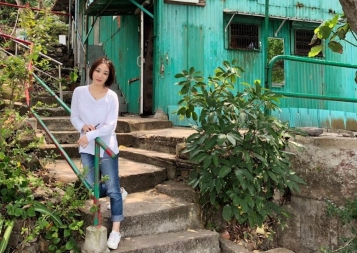 Wenhan Lu sitting on the steps of her home