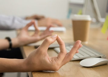 Hands of employee at the work place in meditative posture