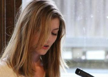 Professional Writing Community Impact Scholarship winner Adelle Brunstad reading her work at an event. Photo.