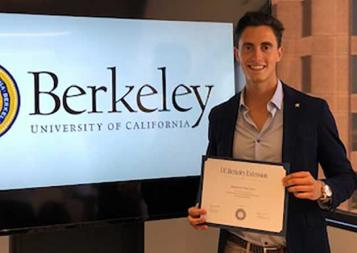 Photo of Alejandro Ruiz holding certificate of completion in front of a TV screen with Berkeley logo